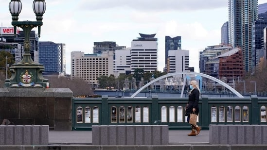 A lone woman, wearing a protective face mask, walks across a city centre bridge as the state of Victoria looks to curb the spread of a coronavirus disease (COVID-19) outbreak in Melbourne, Australia(REUTERS)