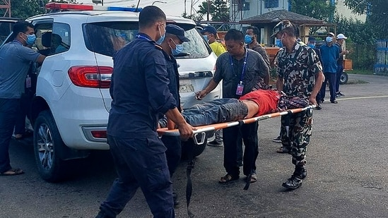 Police and army personnel carry an injured passenger to a hospital in Nepalgunj, some 650 km west of Kathmandu on October 12, 2021, after being airlifted from the Mugu region.(AFP)