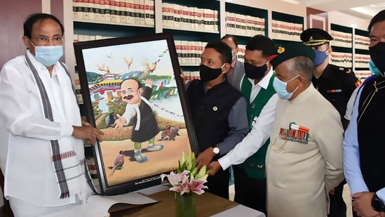 Vice President M Venkaiah Naidu receives an artwork from the speaker of Arunachal Pradesh Assembly Pasang Dorjee Sona, depicting Naidu in Memba traditional attire, on Saturday.(PTI)