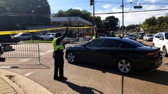 Officers allow a police vehicle to pass under yellow crime scene tape on a street in front of the post office in Memphis. Police said they are investigating a shooting at the post office in Tennessee. (AP Photo/Adrian Sainz)