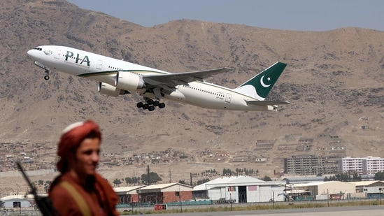 A Taliban fighter stands guard as a Pakistan International Airlines plane takes off with passengers onboard at the airport in Kabul.(AFP)