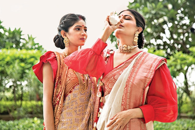 Everything is sacred about pujo, including the sound of the shankha that symbolises the sacred Om sound. Aakashi and Ananya Ghosh learn blowing the shankha as they prepare for the festival. They have taken out sarees from their thakuma'a old trunk - ivory khinkhwab saree embellished with red Banarasi border in ghatchola pattern and cream and red georgette bandhani saree with a golden intricate weave. For a fun twist, they pair the saris with pretty blouses that have puffed sleeves. (Photo: Akhil Verma)