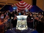 Visitors at the National Museum look at a display of the lunar rock samples retrieved from the moon by China's Chang'e 5 lunar lander late last year in Beijing.(AP Photo/Ng Han Guan, File)