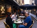 People dine outdoors in Degraves Street in Melbourne, Friday, Oct. 22, 2021. Melbourne, Australia's most populous city after Sydney, came out of 77 days of lockdown on Friday after Victoria state reached a benchmark of 70% of the target population fully vaccinated.(Daniel Pockett/AAP Image via AP)