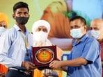 Delhi chief minister Arvind Kejriwal felicitates a student during Valmiki Jayanti celebration, at Thyagraj stadium, in New Delhi, on Saturday. (HT)