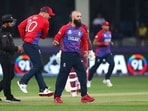 England's Moeen Ali, right, celebrates after taking the wicket of West Indies' Lendl Simmons caught by England's Liam Livingstone during the Cricket T20 World Cup match between England and the West Indies at the Dubai International Cricket Stadium, in Dubai, UAE, Saturday, Oct. 23, 2021.(AP)