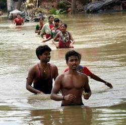 People move to safer places after flood waters submerged their village in Udaynarayanpur in Howrah district of West Bengal on Thursday.