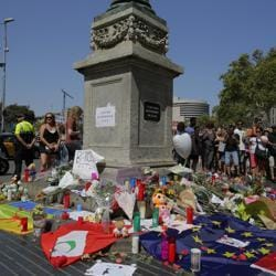 People place flags, messages and candles after a van attack killed 14 people in Barcelona, Spain, on August 17, 2017.