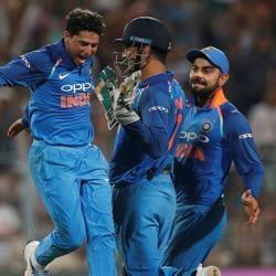 Kuldeep Yadav (L) celebrates with his Indian cricket teammates after dismissing Australia's Pat Cummins during the second ODI in Kolkata.
