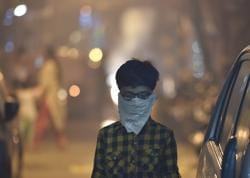 A child protects his face amid heavy smog due to bursting of firecrackers despite the ban imposed by the Supreme Court to control the air pollution following Diwali celebrations in New Delhi on Thursday.
