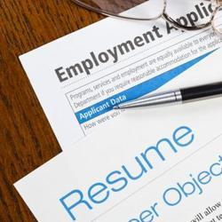 Employment application and resume on table with glasses and pen.