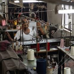 In this picture taken on September 25, 2017, a man works at a garment factory in Ludhiana. Over the last year, Prime Minister Narendra Modi has rolled out controversial reform measures that have affected small traders.