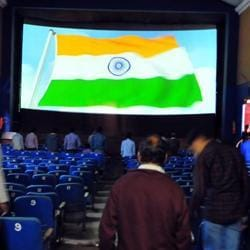 People stand for the national anthem at a cinema hall in Indore.
