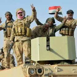 Iraqi forces show victory signs after they captured Rawa town, the last remaining town under Islamic State control, in Iraq on November 17, 2017.