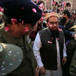 Hafiz Saeed is showered with flower petals as he walks to court before a Pakistani court ordered his release from house arrest in Lahore, Pakistan.