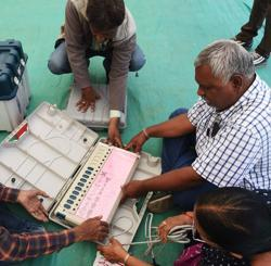 Officials check an Electronic Voting Machine (EVM) ahead of the second phase of Gujarat Vidhan Sabha elections in Ahmedabad on December 13, 2017.