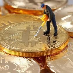 A small toy figure is seen on representations of the Bitcoin virtual currency in this illustration picture.