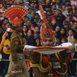 An Indian Border Security Force soldier carries the national flag as he and others take part in the daily beating of the retreat ceremony at the India-Pakistan Wagah Border Post near Amritsar, on December 24, 2017.