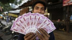 A man displays new currency notes in Ahmadabad/(AP File Photo)