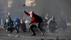 A Palestinian protester uses a sling to hurl stones towards Israeli troops during clashes as Palestinians call for a