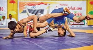Solapur's Saurabh Igave of Maharashtra (red) in action against Aman of Haryana on the last day of the 37th sub-junior national wrestling at Shiv Chhatrapati sports complex in Balewadi.(SANKET WANKHADE/HT PHOTO)