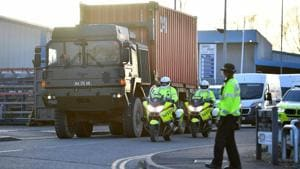 Police officers escort an army truck, carrying a freight container laden with the car of Sergei Skripal, as it is driven from the Churchfields industrial estate in Salisbury, southern England on Friday as part of investigations in connection with the poisoning of the former Russian spy.(AFP)