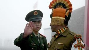 """A Chinese soldier gestures to an Indian soldier at a border crossing between India and China. India's envoy Gautam Bambawale in an interview to Hong Kong-based South China Morning Post had blamed China for the stand-off in Doklam saying it happened because Beijing tried to alter the """"status quo"""" which it should not have.(AFP File Photo)"""