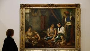 A woman looks at the painting Femmes d'Alger dans leur appartement at the exhibition