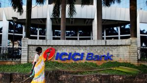 File photo of a municipal worker walking past a logo of ICICI Bank at its headquarters in Mumbai.(Reuters photo)