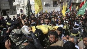 Relatives and Fateh masked militants carry the body of Hamdan Abu Amsha, 23, during his funeral in Beit Hanoun, Gaza Strip, on Saturday.(AP photo)