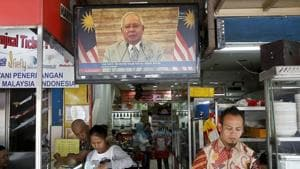 Passerby walks in front of a live broadcast of an announcement by Malaysian Prime Minister Najib Razak at a restaurant in Kuala Lumpur, Malaysia, on April 6, 2018.(AP)