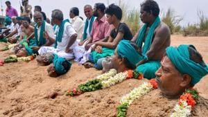 Farmers representing National South Indian River Link Association lie neck deep in Cauvery river bed with rose garlands to signify 'death' as part of their protest demanding the constitution of the Cauvery Water Management Board, Tiruchirappalli, Tamil Nadu, April 6(PTI)