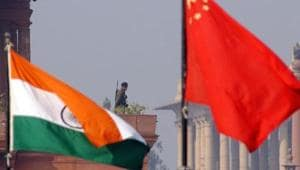An Indian paramilitary officer is framed by an Indian (L) and Chinese (R) flags as he stands guard near the presidential palace in New Delhi.(AFP FILE)