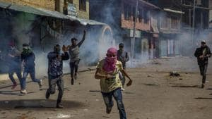 Kashmiri villagers run for cover as government forces fire pellets and tear gas at them after they were stopped from taking part in the funeral procession of Kashmiri militant Mussavir Wani in Pulwama, on April 7.(AP file photo)