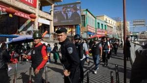 Armed civilians patrol the area outside the Hotan Bazaar where a screen shows Chinese President Xi Jinping in Hotan in western China's Xinjiang region.(AP File Photo)