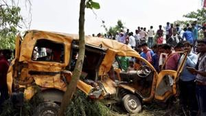 People gather around the mangled school van which collided with a moving train in Kushinagar on Thursday.(PTI Photo)