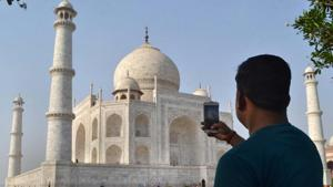 A man clicks a picture of Taj Mahal in Agra on Tuesday.(PTI)