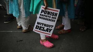 A woman stands with a placard during a protest against rapes, in New Delhi on May 5.(AP FILE)