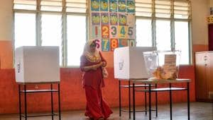 A Malaysian woman casts her vote during the 14th general election at a polling station in Kuala Lumpur on May 9, 2018.(AFP)