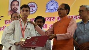 Class 12 overall topper Lalit Pancholi getting his gold medal from CM Shivraj Singh Chouhan in Bhopal, India, on Monday, May 14.(Mujeeb Faruqui/HT Photo)