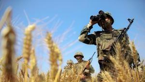 BSF personnel uses binoculars to maintain vigil along the international border in Jammu.(PTI File Photo)