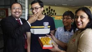 Prakhar Mittal, who secured first spot in CBSE's Class 10th examinations along with Nandini Garg, Rimzhim Aggarwal and Sreelakshmi G, being offered sweets by his parents in Gurugram on Tuesday.(PTI Photo)