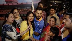 Visitors pose for photographs next to a wax figure of Indian cricket captain Virat Kohli during its unveiling at Madame Tussauds wax museum in New Delhi.(AP)