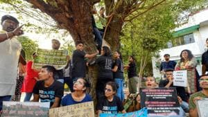 Activists from various environmental organisations display placards and hold a tree during a protest against cutting of trees in Nauroji Nagar area, in New Delhi on Sunday.(PTI Photo)