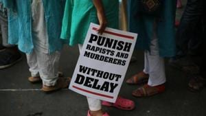A protestor stands with a placard during a protest against two recently reported rape cases as they gather near the parliament in New Delhi.(AP File Photo)