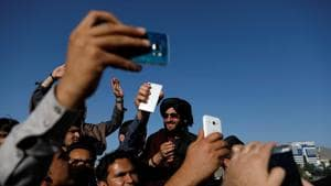 Afghans take pictures with Taliban members, Kabul, June 16(REUTERS)