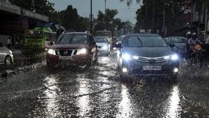 Vehicles ply on a road as it rains in New Delhi.(PTI Photo)