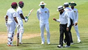 Dinesh Chandimal (C) of Sri Lanka looks at the ball in umpire Aleem Dar's hand while Shai Hope (L) and Devon Smith (2L) of West Indies watch during day 3 of the 2nd Test between West Indies and Sri Lanka at Daren Sammy Cricket Ground, Gros Islet, St. Lucia, on June 16, 2018.(AFP)
