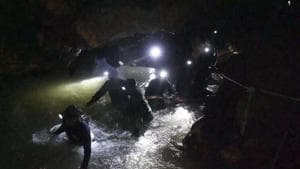 In this handout file photo released by Tham Luang Rescue Operation Center, Thai rescue teams walk inside cave complex where 12 boys and their soccer coach went missing in Mae Sai, Chiang Rai province, northern Thailand.(AP)