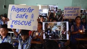 Schoolchildren hold placards and pictures during a prayer event for the safe rescue of young football players and their coach stuck in a cave in Thailand, in Ahmedabad on July 9, 2018.(AFP)